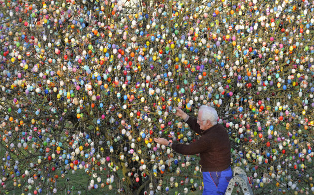 FILE - In this March 21, 2012 file picture Volker Kraft decorates a tree with 10,000 Easter eggs in the garden of the retired couple Christa and Volker Kraft in Saalfeld, Germany. The Kraft family has