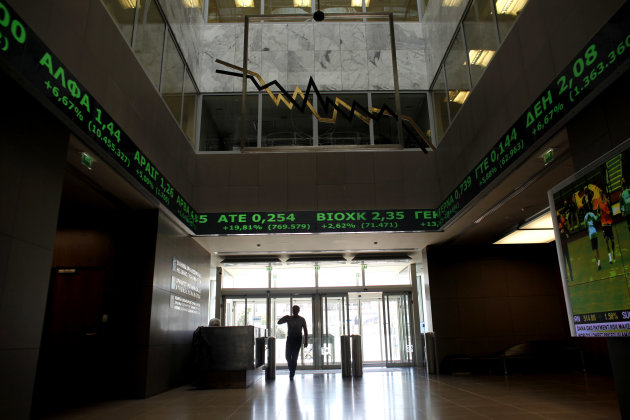 A man walks  as above  screens show rising stocks in green at the Greek Stock Exchange in Athens, on Monday , June 18, 2012. In Athens, stocks lost initial strong gains but were still 4.5 percent up i