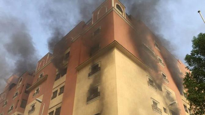 In this image released by the Saudi Interior Ministry's General Directorate of Civil Defense, smoke billows from a fire at a residential complex used by state oil giant Saudi Aramco in Khobar, Saudi Arabia, Sunday, Aug. 30, 2015. Authorities say one person has been killed and dozens were injured in the fire. (Saudi Interior Ministry General Directorate of Civil Defense via AP)