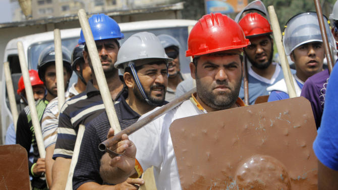 Supporters of Egypt's Islamist President Mohammed Morsi hold sticks and wear protective gear during training outside of the Rabia el-Adawiya mosque near the presidential palace, in Cairo, Egypt, Tuesday, July 2, 2013. Egypt was on edge Tuesday following a 'last-chance' ultimatum the military issued to Mohammed Morsi, giving the president and the opposition 48 hours to resolve the crisis in the country or have the army step in with its own plan. Protesters seeking the ouster of the Islamist president remained camped out at Cairo's Tahrir Square, the birthplace of the 2011 uprising, gearing up for a third day of anti-Morsi rallies. Across town, Morsi's Islamist backers have hunkered down at their own rally site, vowing to resist what they depict as a threat of a coup against a legitimately elected president. (AP Photo/Amr Nabil)