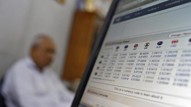 A man sits next to a computer screen showing the Indian currency rates inside a private money exchange office in New Delhi