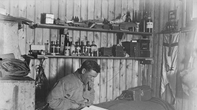 A self-portrait of scientist George Murray Levick smoking a pipe and reading on his bunk in the hut at Cape Adare, Antarctica