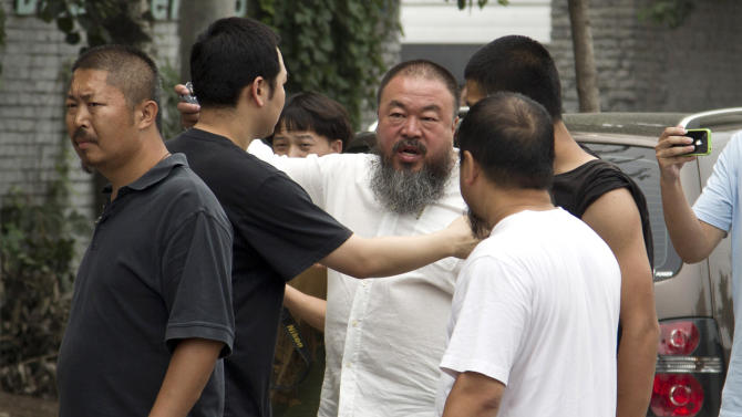 Ai Weiwei, third from right, argues with a policeman, center, outside his home in Beijing Wednesday, June 20, 2012. Chinese police on Wednesday barred Ai from attending the first hearing of a lawsuit brought by his company against Beijing tax authorities and blocked reporters from filming at the courthouse, part of an intimidation campaign aimed at silencing the prominent artist and outspoken government critic. (AP Photo/Andy Wong)