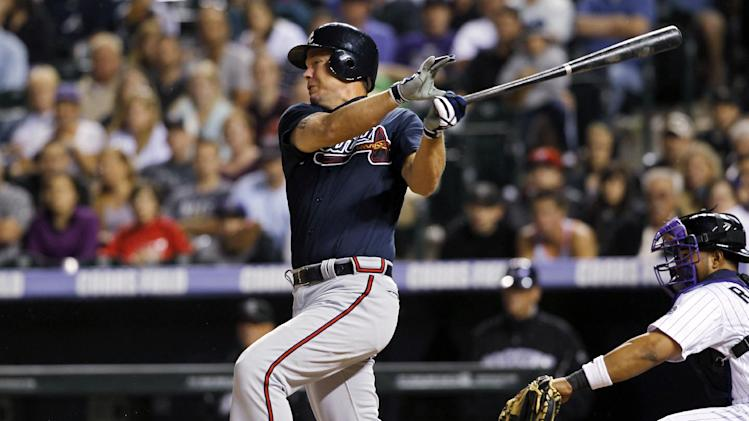 Atlanta Braves' Chipper Jones follows through with his swing after hitting a single to bring in two runners as Colorado Rockies catcher Wilin Rosario watches in the seventh inning of a baseball game in Denver, Saturday, May 5, 2012. (AP Photo/David Zalubowski)