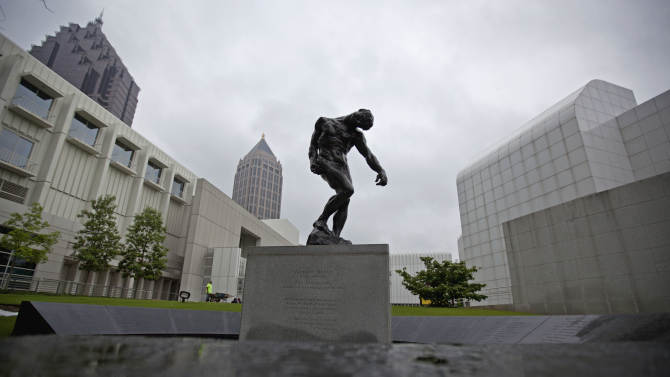 """In this May 9, 2012 photo, a casting of sculptor Auguste Rodin's """"The Shade"""" stands on the grounds of Atlanta's High Museum of Art in a memorial to the victims of the June 3, 1962 crash at Orly Field in Paris that killed 100 of Atlanta's cultural leaders. The statue is ringed by polished stone etched with the names of those who died. (AP Photo/David Goldman)"""