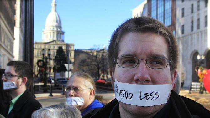 Protesters hold a  silent protest in Lansing, Mich., Wednesday, Dec. 12, 2012, a day after thousands of protesters rallied on the grounds as lawmakers pushed final versions of right-to-work legislation. The tape over their mouths shows how Gov. Rick Snyder and his allies have silenced Michigan's middle class, and effectively cut the wages of Michiganders by $1500. (AP Photo/Carlos Osorio)