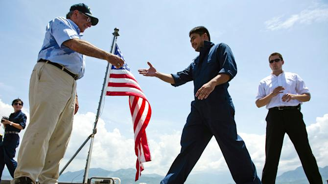U.S. Secretary of Defense Leon Panetta, left, hands out coins to members of the crew as he visits USNS Richard E. Byrd in Cam Ranh Bay, Vietnam, Sunday, June 3, 2012. Panetta toured the former U.S. air and naval base in the bay, becoming the most senior American official to go there since the war ended. (AP Photo/Jim Watson, Pool)