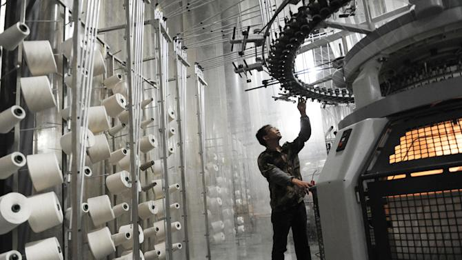 A labourer works on the assembly line at a clothing factory in Bozhou, east China's Anhui province, on May 22, 2014
