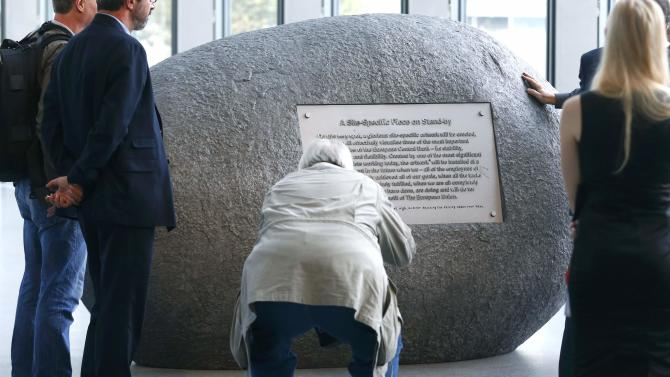 Visitors look at the sculpture 'The Stone' by Bulgarian artist Nedko Solakov during it's inauguration inside new headquarters of ECB in Frankfurt