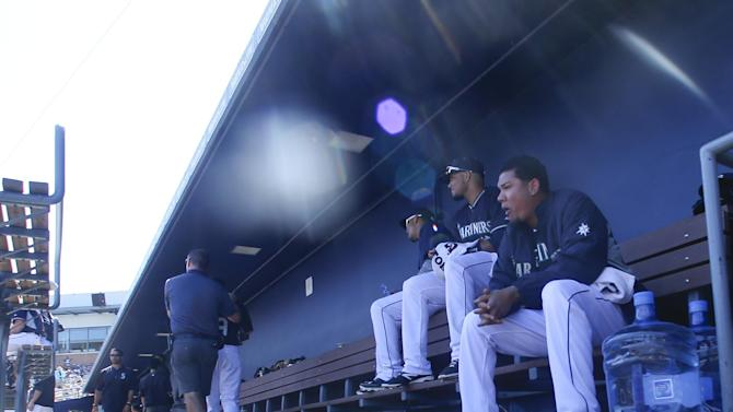 Seattle Mariners starting pitcher Felix Hernandez, right,  sits in the dugout between innings of his start against the Kansas City Royals in a spring training baseball game Thursday, March 26, 2015, in Peoria, Ariz. Hernandez pitched six innings and allowed one and two hits but took the loss in the game won by the Royals 3-0.  (AP Photo/Lenny Ignelzi)