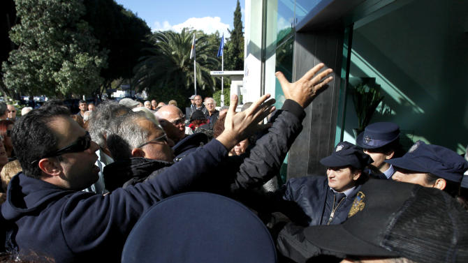 Investors, left, shout in front of police officers outside the Cyprus' parliament during a protest in Nicosia, Tuesday, Dec. 11, 2012. The investors, who bought securities in the country's troubled banks, say they want their money back after the banks blocked access to their cash after losing billions on bad Greek debt and loans. Cyprus has reached a preliminary deal with international creditors on a multi-billion euro bailout to rescue its banks and to make its payments. Final approval of the agreement with the European Commission, the European Central Bank and the International Monetary Fund could be more than a month away. (AP Photo/Petros Karadjias)