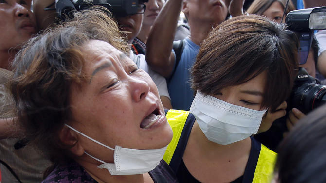 A relative, left, of a victim in the TransAsia Airways flight GE222 crash cries during a funeral service on the Taiwan island of Penghu, Friday, July 25, 2014. Stormy weather on the trailing edge of Typhoon Matmo was the likely cause of the plane crash that killed more than 40 people, the airline said Thursday. (AP Photo/Wally Santana)
