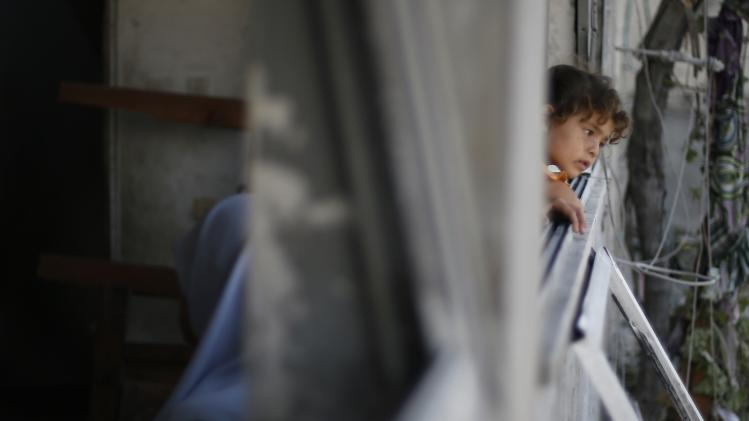 Palestinian girl looks out the window of her family's house, which witnesses said was damaged in an Israeli air strike, in Gaza City