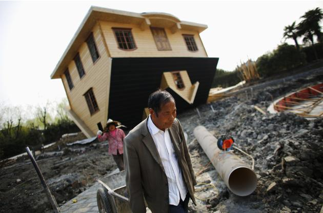 Labourers work at an upside-down house under construction at Fengjing Ancient Town, Jinshan District