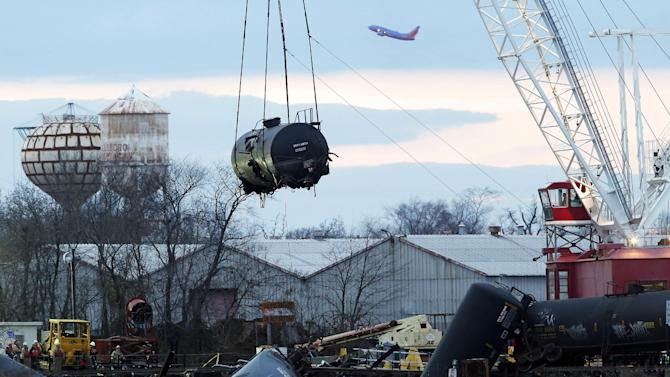 A train tank car dangles from a crane as it is pulled up from the crash site on a small bridge on the Mantua Creek, Tuesday, Dec. 11, 2012, in Paulsboro, N.J. The tank car was the first to be removed as officials continued to clean up after the accident. Hazardous gas spewed from a ruptured freight train car during the accident, which occurred Nov. 30, 2012. Precautionary evacuations were ordered late after readings showed higher levels of vinyl chloride in the air. (AP Photo/Julio Cortez)