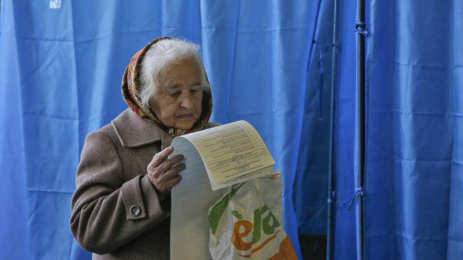 An elderly voter looks at her ballot at a polling station during parliamentary elections in Kiev, Ukraine, Sunday, Oct. 26, 2014. Voters in Ukraine headed to the polls Sunday to elect a new parliament, overhauling a legislature tainted by its association with ousted President Viktor Yanukovych.(AP Photo/Efrem Lukatsky)