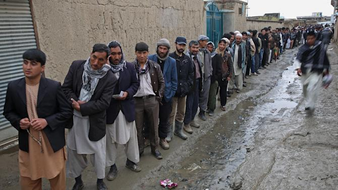 Afghan men line up for registration process before they cast their votes at a polling station in Kabul, Afghanistan, Saturday, April 5, 2014. Afghans flocked to polling stations nationwide on Saturday, defying a threat of violence by the Taliban to cast ballots in what promises to be the nation's first democratic transfer of power. (AP Photo/Massoud Hossaini)