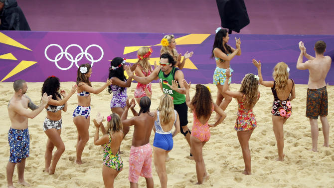 Germany's Jonathan Erdmann enters the court past dancers at the start of their men's preliminary round beach volleyball match against the Netherlands at the London 2012 Olympic Games at Horse Guards Parade