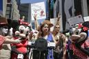 "Lucia Gomez, center, executive director of La Fuente, speaks during a press conference, Tuesday, Aug. 19, 2014 at Times Square in New York. Gomez lead the gathering that called for the fair treatment and the right for performers to work as costumed characters. Gomez said, ""These are individuals who bring smiles to the world."" (AP Photo/Vanessa A. Alvarez)"