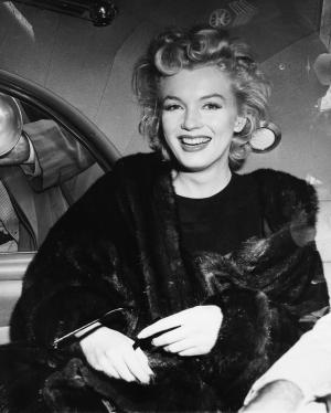 FILE - In this June 2, unknown year, file photo, actress Marilyn Monroe smiles in a car after arriving tousled from an all-night plane flight from Hollywood to Idlewild Airport, in New York. The actress said she planned to rest in New York before going to England to make a new movie with Sir Laurence Olivier. In late 2012, the FBI has released a new version of files it kept on Monroe that reveal the names of some of her acquaintances who had drawn concern from government officials and members of her entourage over their suspected ties to communism. (AP Photo, File)