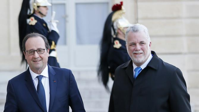 French President Hollande welcomes Quebec Premier Couillard before a meeting at the Elysee Palace in Paris