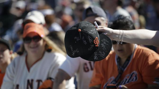 A fans holds a San Francisco Giants hat before a spring training baseball game between the San Francisco Giants and Chicago Cubs, Thursday, March 5, 2015, in Scottsdale, Ariz. (AP Photo/Darron Cummings)