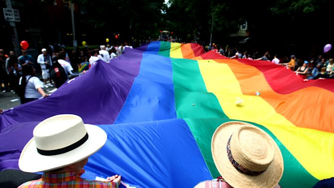FILE - Participants march with a rainbow flag during Seattle's annual Gay Pride Parade on Sunday, June 24, 2012. Even as they acknowledge greater acceptance by society, lesbian, gay, bisexual and transgender Americans are, on average, less happy than other U.S. adults, and many report instances of rejection and harassment, according to a sweeping new survey. The survey, released Thursday, June 13, 2013 by the Pew Research Center, is one of the largest and most detailed ever conducted among LGBT respondents by a major U.S. polling organization. (AP Photo/seattlepi.com, Joshua Trujillo)