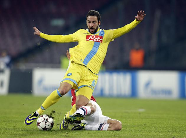 Napoli forward Gonzalo Higuain of Argentina, left, is tackled by Arsenal's Tomas Rosicky, during a Champions League, group F soccer match, at the Naples San Paolo stadium, Italy, Wednesday, Dec. 1