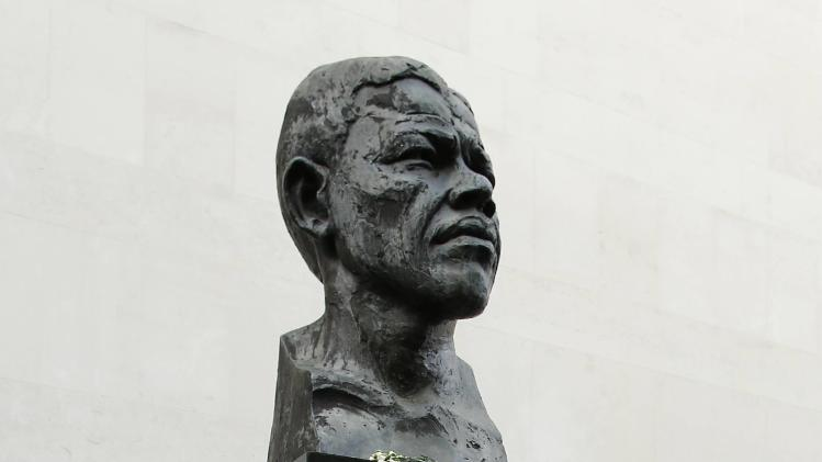 A boy looks at a sculpture of South Africa's former president Nelson Mandela on the South Bank in central London