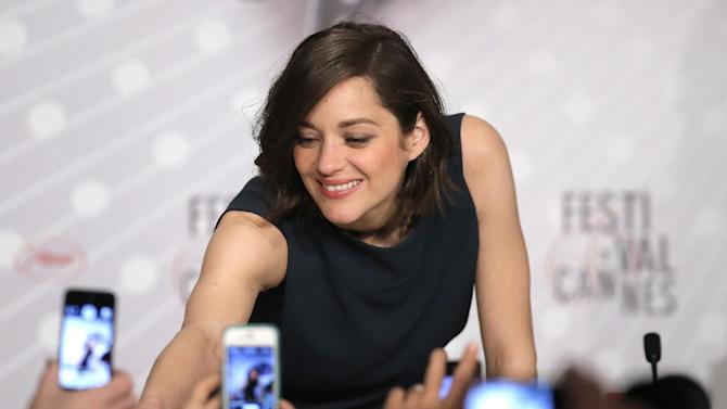 Actress Marion Cotillard signs autographs for fans as she arrives for the press conference of Blood Ties at the 66th international film festival, in Cannes, southern France, Monday, May 20, 2013. (AP Photo/Francois Mori)