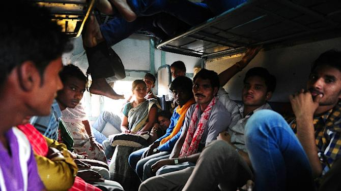 Indian passengers sit inside a crowded train carriage at Allahabad Junction in Allahabad on February 26, 2015