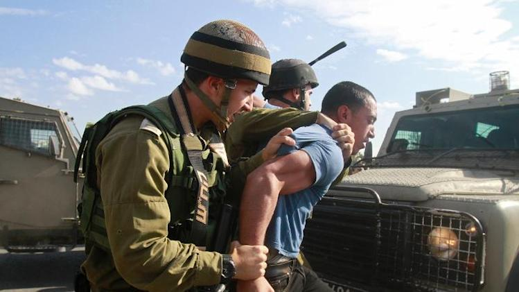 Israeli security forces detain a Palestinian protester during a demonstration against Israeli settlers near the West Bank village of Bethlehem, on November 22, 2013