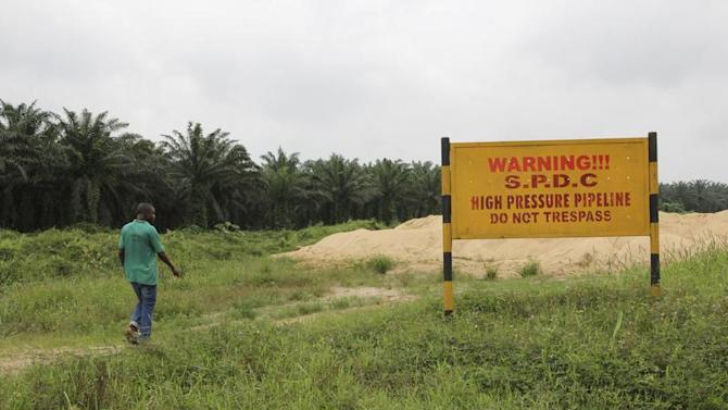 A man walks past a signboard erected along the right of way of Royal Dutch Shell in the Delta region