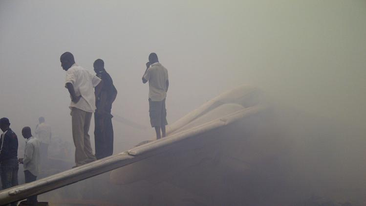 Onlookers stand on the tail wing of a crashed passenger plane in a neighborhood just north of Murtala Muhammed International Airport, in Lagos, Nigeria, Sunday, June 3, 2012.  The passenger plane carrying more than 150 people crashed in Nigeria's largest city on Sunday, government officials said. The Lagos state government said in a statement that 153 people were on the Dana Air flight Sunday.(AP Photo/Jon Gambrell)