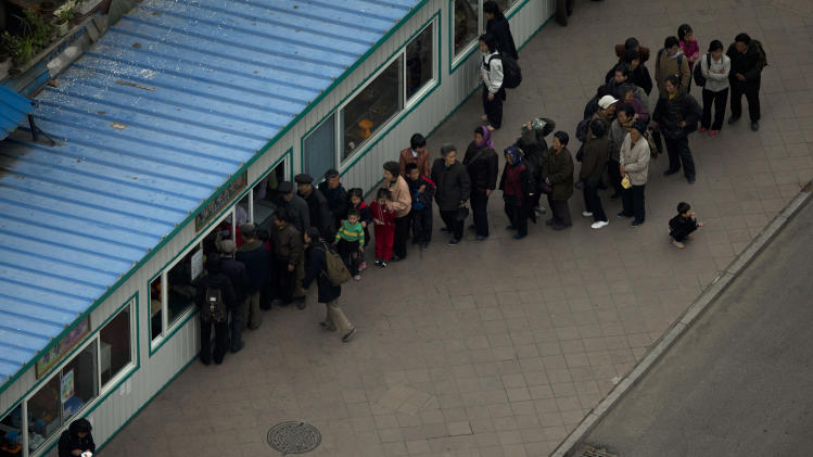 People line up outside a window of a food shop in Pyongyang, North Korea, Tuesday, April 16, 2013. (AP Photo/Alexander F. Yuan)