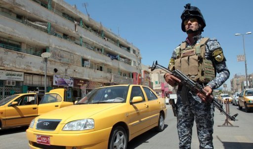 An Iraqi policeman stands guard at a checkpoint in central Baghdad on August 4. Attacks mainly targeting Iraqi security forces killed five people, among them four policemen, and wounded 16 on Sunday, security and medical officials said