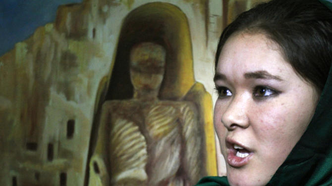 Afghan model Farkhunda Taheri, 17,  speaks during an interview with The Associated Press next to a painting of Bamiyan's statue after a fashion show in Kabul, Afghanistan, Friday, Feb. 8, 2013. The rare fashion show in this war-weary capital was a small production but a big idea — part of an Afghan group's efforts to empower women by breaking down barriers in this highly conservative Muslim society. (AP Photo/Musadeq Sadeq)