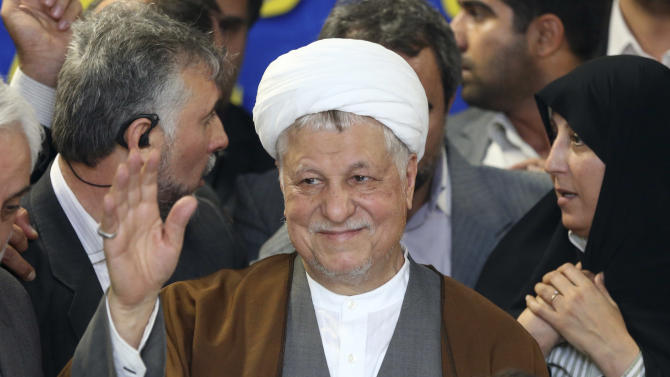 In this picture taken on Saturday, May 11, 2013, former Iranian President Akbar Hashemi Rafsanjani waves to media as he registers his candidacy for the upcoming presidential election, while his daughter Fatemeh, right, looks on, at the election headquarters of the interior ministry in Tehran, Iran. A hardline news website says Iran's election overseers have rejected a pair of powerful and divisive figures from running in next month's presidential election. Tasnimnews.com say Akbar Hashemi Rafsanjani, a former president who still wields enormous influence, and Esfandiar Rahim Mashaei, a close confident of President Mahmoud Ahmadinejad, have been barred by the Guardian Council. (AP Photo/Ebrahim Noroozi)