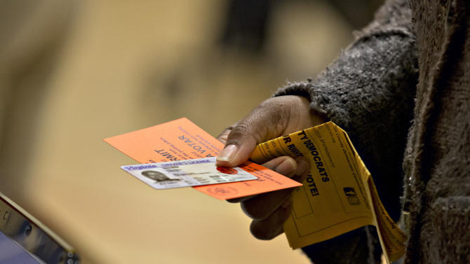 FILE - In this Nov. 6, 2012 file photo, a voter holds their voting permit and ID card at the Washington Mill Elementary School near Mount Vernon, Va. Across the South, Republicans are working to take advantage of a new political landscape after a divided U.S. Supreme Court freed all or part of 15 states, many of them in the old Confederacy, from having to ask Washington's permission before changing election procedures in jurisdictions with histories of discrimination. (AP Photo/J. Scott Applewhite, File)