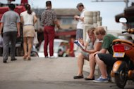 Tourists consult a map at as they sit on a street in Beijing on July 12. Bad news from South Korea, Singapore and China this week failed to rattle investors' confidence in the region, despite fears that Europe's economic contagion is spreading rapidly to the East