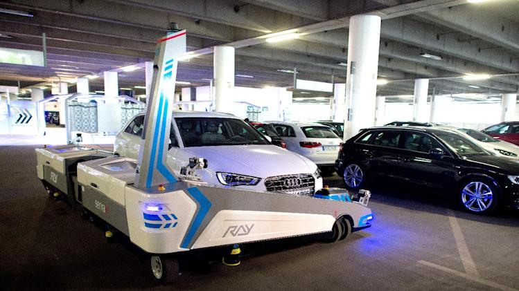 """Parking robot """"Ray"""" transports a car in Duesseldorf, Germany, Monday, 23 June 2014. The parking robot will see service for the first time at Duesseldorf Airport. (AP Photo/dpa, Federico Gambarini)"""