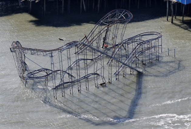 "FILE - In this Friday, Nov. 9, 2012 file photograph, the roller coaster from an amusement pier rests in the Atlantic Ocean in Seaside Heights, N.J., after the region was pounded by Superstorm Sandy. The remains of the roller coaster that was knocked off a New Jersey amusement pier by Superstorm Sandy and partially submerged in the Atlantic Ocean might be left there as a tourist attraction. Seaside Heights Mayor Bill Akers tells WNBC-TV in New York that officials have not made a decision on whether to tear down the coaster. But the mayor says he's working with the Coast Guard to see if the coaster is stable enough to leave it alone because he believes it would make ""a great tourist attraction."" (AP Photo/Mel Evans)"