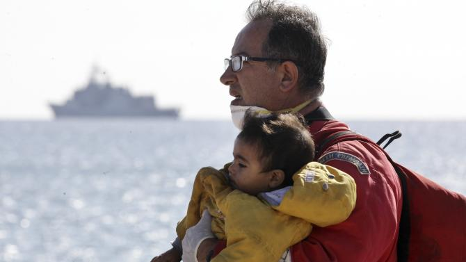 A rescuer carries a child evacuated from a cargo ship, in Ierapetra in the island of Crete
