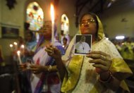 Roman Catholic women hold candles and pictures of the newly elected Pope Francis during a thanksgiving mass in his honour at a church in Kolkata March 17, 2013. REUTERS/Rupak De Chowdhuri
