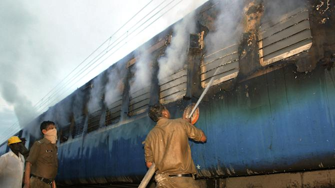 An Indian fire official douses fire coming out from a coach of a passenger train at Nellor nearly 500 kilometers (310 miles) south of Hyderabad, India, Monday, July 30, 2012. A fire swept through a train car packed with sleeping passengers in southern India on Monday, killing at least 47 people and sending panicked survivors rushing for the only clear exit once the train stopped, officials said. (AP Photo)