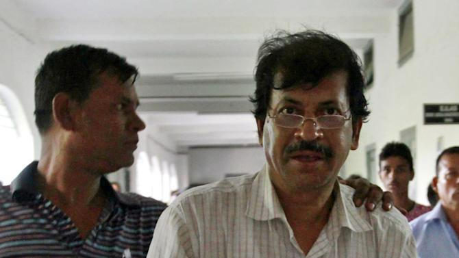 In this May 3, 2013 photo, engineer Abdur Razzak Khan, right, is detained by police in Dhaka, Bangladesh. The death toll in the factory-building collapse in Bangladesh rose to more than 530 on Saturday.  Police official Ohiduzzaman said Friday that engineer Abdur Razzak Khan was arrested a day earlier on a charge of negligence related to the building collapse. He said Khan worked as a consultant to Rana Plaza owner Mohammed Sohel Rana when the illegal three-floor addition was made to the building. (AP Photo)