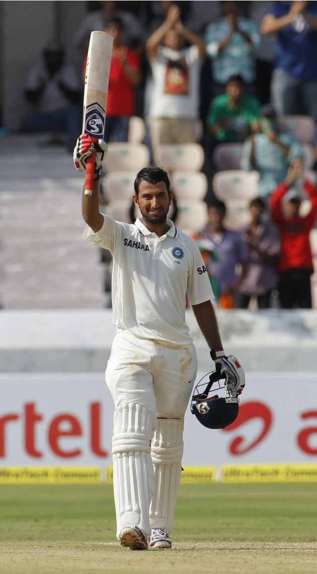 India's Pujara raises his bat to celebrate scoring a century during the first day of their first test cricket match against New Zealand in Hyderabad