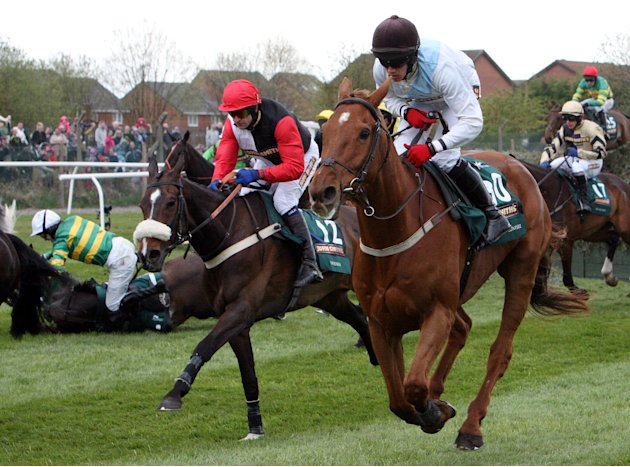 Synchronised, ridden by Tony McCoy, left, falls after jumping Becher's Brook the Grand National at Aintree Racecourse, Liverpool, England, Saturday April 14, 2012. Synchronised, who won the Cheltenham