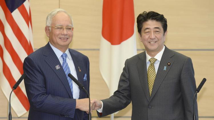Japan's PM Abe shakes hands with his Malaysian counterpart Razak at the end of a media announcement after their talks at Abe's official residence in Tokyo