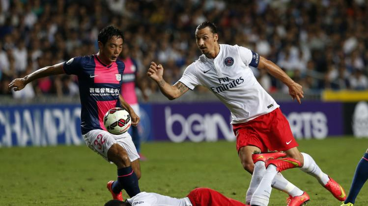 Paris Saint-Germain's Ongenda lies on ground as Ibrahimovic and Jang Kyung-jin from local team Kitchee battle for ball during friendly match in Hong Kong